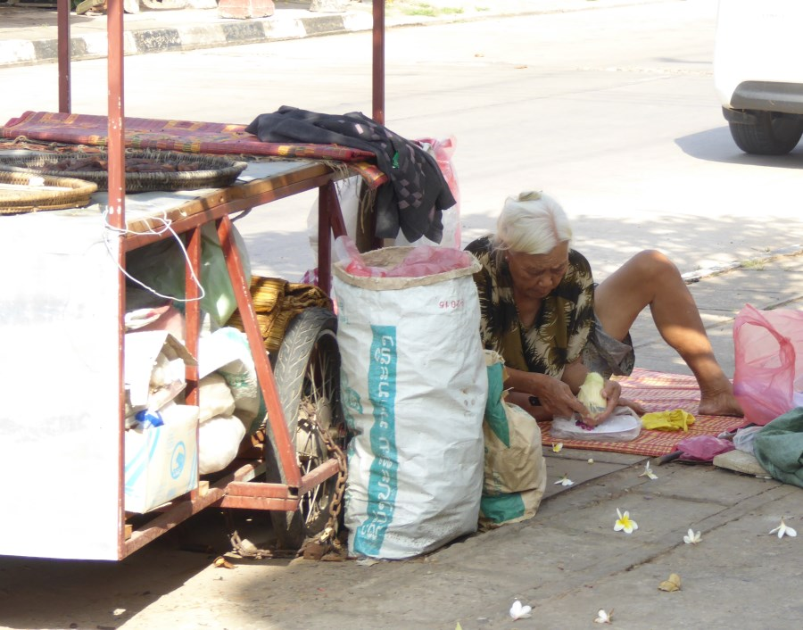 This old lady peels away at pineapples (just like my grandfather was taught to do in Indonesia) to sell and make a living.