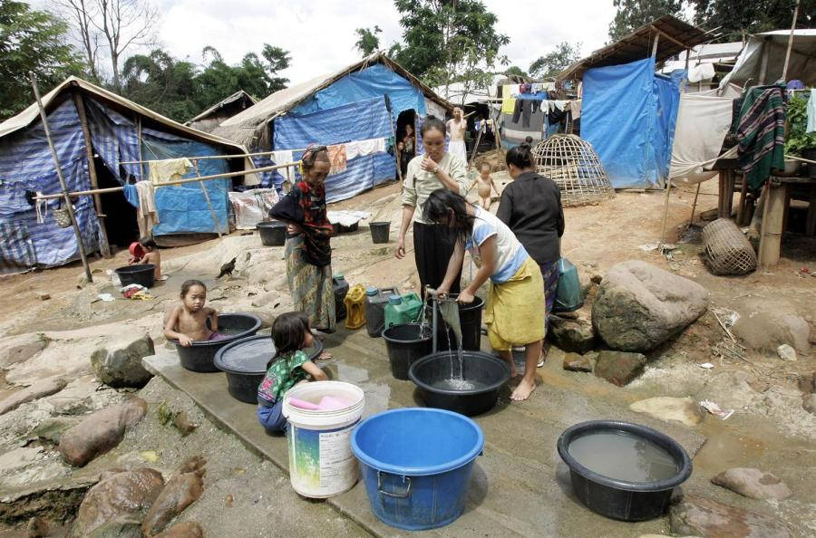 Hmong refugees collect water at Huay Nam Khao village in Thailand's northeastern province of Petchabun